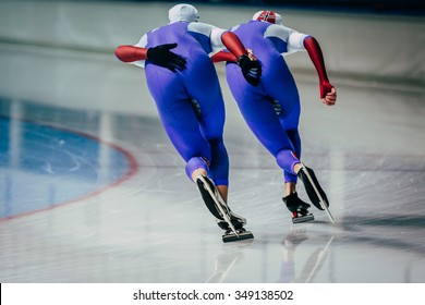 closeup two men skaters synchronous running during warm-up before competitions in speed skating
