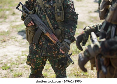 Close-up of two military men in green camouflage. Soldiers hold AK47 assault rifles in their hands. Defensive unit
