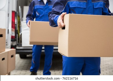 Close-up Of Two Mover's Hand In Uniform Carrying Cardboard Box