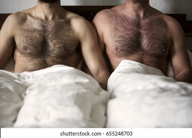 closeup of two naked men with hairy chest in bed