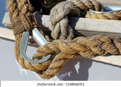 Closeup of two nautical ropes connected together: one with simple eye splice and one with eye splice with thimble