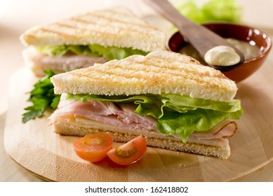 Closeup of two panini sandwiches with turkey, cheese and lettuce.