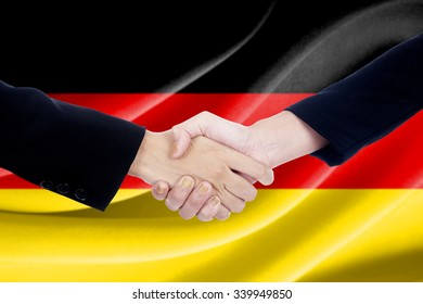 Closeup of two people in formal suit, shaking hands in front of Germany flag