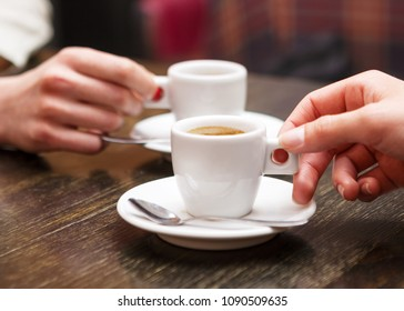 Closeup of two people holding cups of coffee sitting in cafeteria.