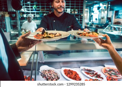 Close-up of two plates with seafood and delicious vegetables, served by an experienced chef to a couple at the counter of a trendy restaurant with fresh nutritious food