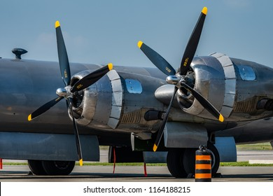 A closeup of two powerful radial engines on a vintage warplane with the motionless propellers waiting to power to life.