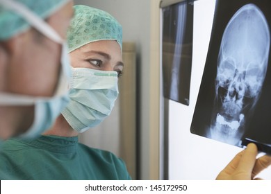 Closeup of two radiologists examining xray of skull