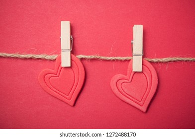 closeup of two red hearts on clothespins on red background - Valentine's day concept