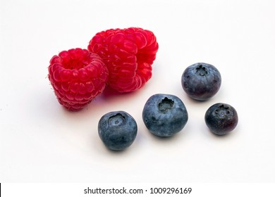 Closeup of Two Red Raspberries and Four Plump Blueberries on a white background