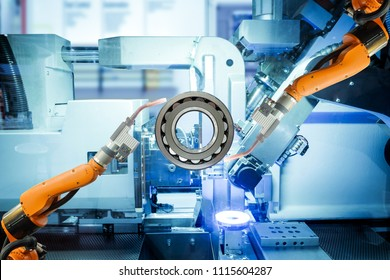 Close-up two robotic welding are working with spherical roller bearing on smart factory, on machine blue tone color background, industry 4.0 and technology.