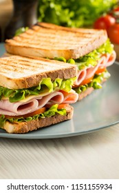 Close-up of two sandwiches with bacon, salami, prosciutto and fresh vegetables on rustic wooden cutting board. Club sandwich concept.