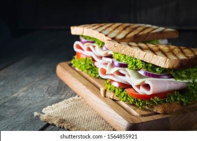 Gros plan sur deux sandwichs au bacon, au salami, au prosciutto et aux légumes frais sur une planche à découper en bois rustique. Concept de sandwich club.