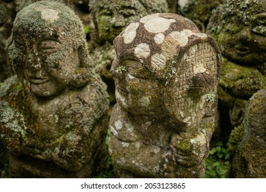 close-up of two sculptures of buddhists covered in moss, one with a tennisracket at the Otagi Nenbutsu-ji temple in Kyoto (Japan), which hosts personalized sculptures of all buddhists who lived there.