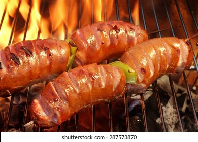 Close-up Of Two Skewers With Sausage On The Hot BBQ Charcoal Grill And Flames In The Background