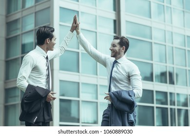 Closeup of two smiling business men high fiving with office building in background