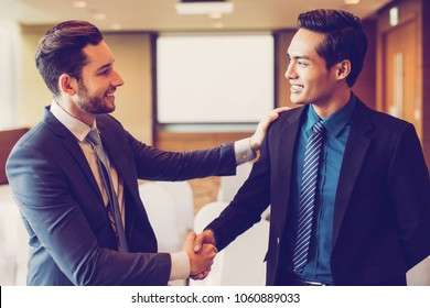Closeup of two smiling middle-aged business men shaking hands and greeting each other in conference room with whiteboard in background