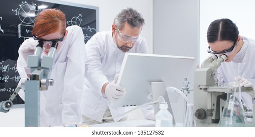close-up of two students in a chemistry lab analyzing under microscope around lab tools and colorful liquids while the teacher is looking on a pc monitor