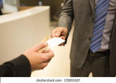 Close-up of two successful business executives exchanging a business card.