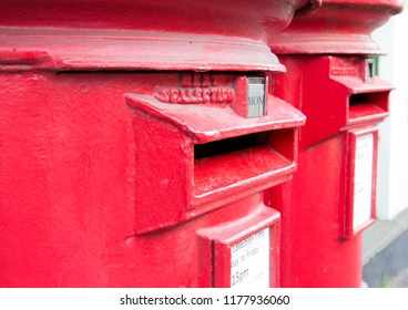 Closeup of two traditional British red mail boxes.