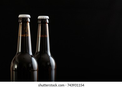 Closeup of two unopened beer bottles isolated on black background