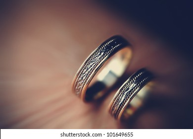 Closeup of two wedding golden rings with magnificent ornate decor on vintage background.