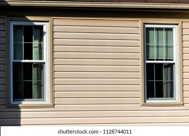Closeup of two windows, wall, exterior of townhouse, townhome with sunlight, light, sunny day