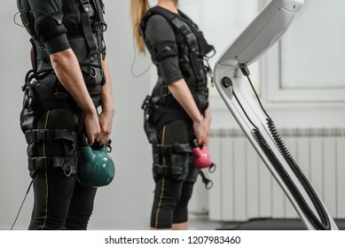 Closeup of two women in EMS suits doing exercises with kettlebell