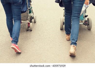 Closeup of two women strolling babies in pushchairs