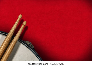 Close-up of two wooden drumsticks and an old metallic snare drum on a red velvet background with copy space. Percussion instrument