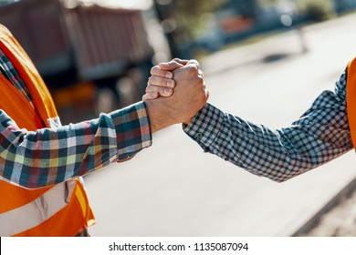 Close-up of two workers shaking hands after completing a job