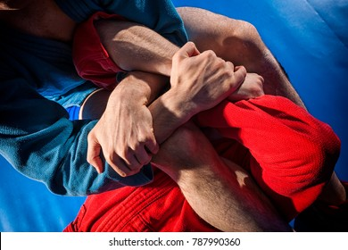 Close-up two wrestlers of grappling and jiu jitsu in a blue and red kimono makes armbar .Submission wrestling   on blue tatami