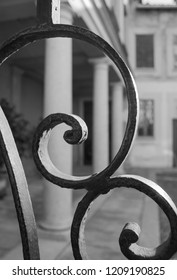 Close-up of two wrought-iron curls of a tall and sturdy gate