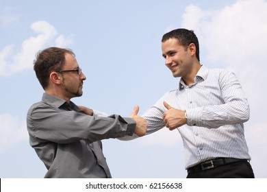 Closeup of two young businessmen showing ok over a deal on sky background
