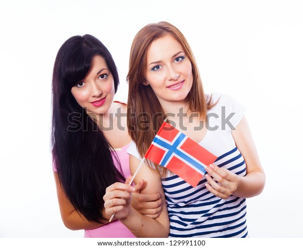 A closeup of two young smiling girls holding a norwegian flag  isolated on white.