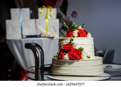 closeup two-tiered white wedding cake decorated with red and pink roses served on glass tray against gift boxes