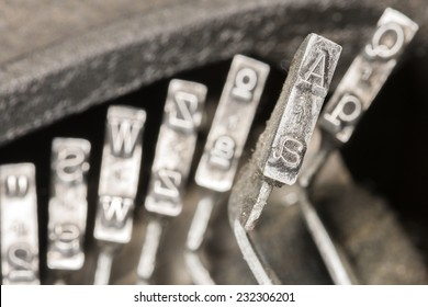 Closeup to typebars of an antique mechanical desktop typewriter with the letter A up