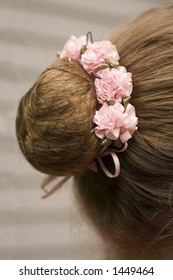 Close-up of a typical ballerina's hairstyle - the bun with rose decorations