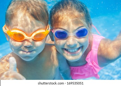 Close-up underwater portrait of the two cute smiling kids