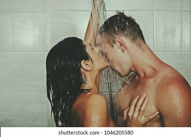 Closeup of undressed sensual pair of young brunette lady embracing and kissing man with beautiful muscular wet body with six-pack and abdoman, horizontal picture. Sensual couple. Bathroom. Sexy photo.