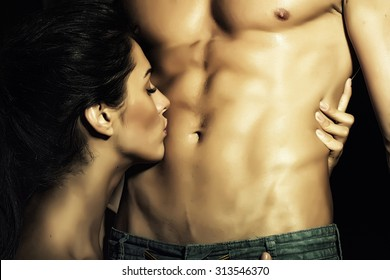 Closeup of undressed sensual pair of young brunette lady embracing and kissing man with beautiful muscular wet body with six-pack and abdoman, horizontal picture