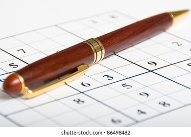 closeup of an unfinished sudoku with elegant pen