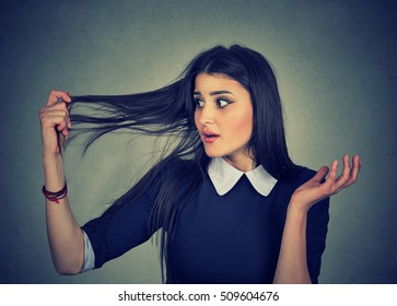 Closeup unhappy frustrated young woman surprised she is losing hair, receding hairline. Gray background. Human face expression emotion. Beauty hairstyle concept