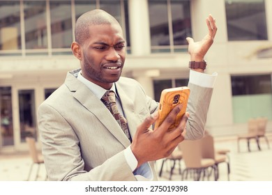 Closeup unhappy young man in suit talking texting on cellphone outdoors. Negative human face expression