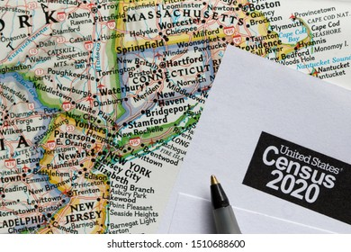 Closeup of United States Census 2020 form informational copy and a ballpoint pen on map.