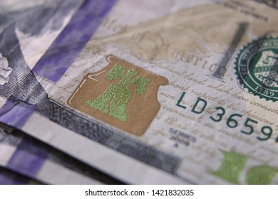 Close-up Of United States One Hundred Dollar Bill With Extreme Narrow Focal Range Highlighting Iridescent Liberty Bell
