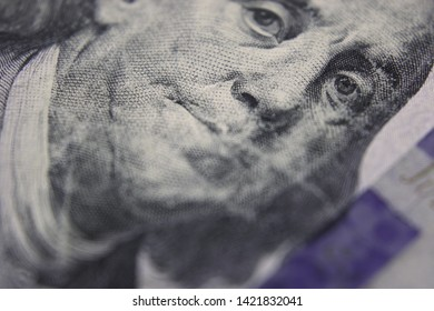 Close-up Of United States One Hundred Dollar Bill With Extreme Narrow Focal Range Highlighting Ben Franklin's Left Eye