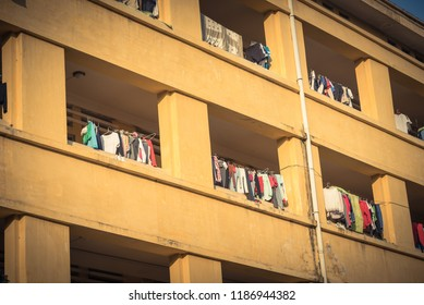 Close-up of university dorm with sun drying hanging clothes line in dense of apartments in Hanoi, Vietnam. Outside view of typical concrete and brick building at sunset. Urban concept.