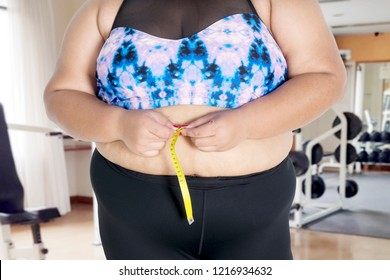 Closeup of an unknown fat woman measuring her waistline by using a measure tape in the gym center