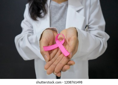 Closeup of unknown female doctor holding pink ribbon. Breast cancer concept