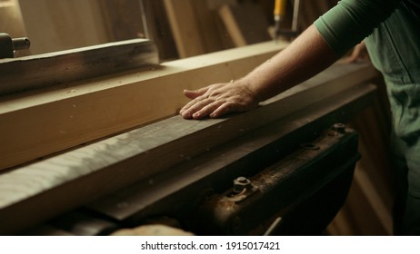 Closeup unknown man grinding wood in carpentry workshop. Unrecognized handyman preparing wooden plank for product indoors. Carpenter working on wood lathe in studio.